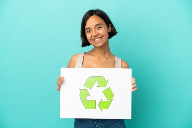 Giovane donna di razza mista isolata su sfondo blu in possesso di un cartello con icona di riciclo con espressione felice
