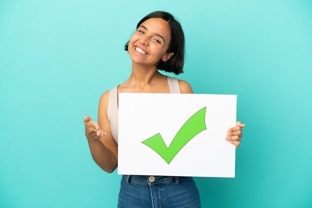 Giovane donna di razza mista isolata su sfondo blu, tenendo un cartello con il testo icona del segno di spunta verde facendo un affare