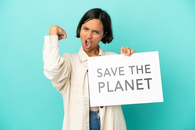 Giovane donna di razza mista isolata su sfondo blu che tiene in mano un cartello con il testo salva il pianeta e fa un gesto forte