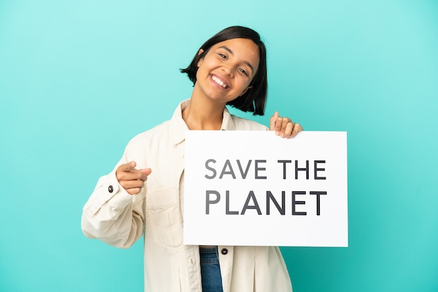 Giovane donna di razza mista isolata su sfondo blu che tiene in mano un cartello con il testo salva il pianeta e indica la parte anteriore