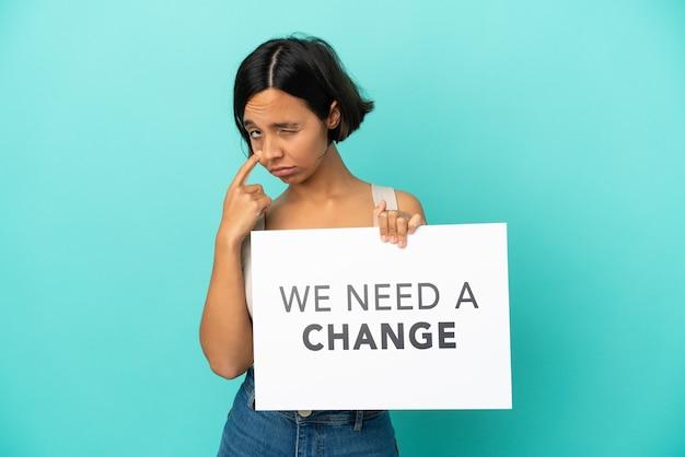 Giovane donna di razza mista isolata su sfondo blu che tiene un cartello con il testo abbiamo bisogno di un cambiamento e mostra qualcosa