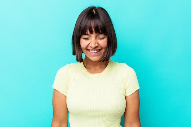 La giovane donna di razza mista isolata su sfondo blu ride e chiude gli occhi, si sente rilassata e felice.