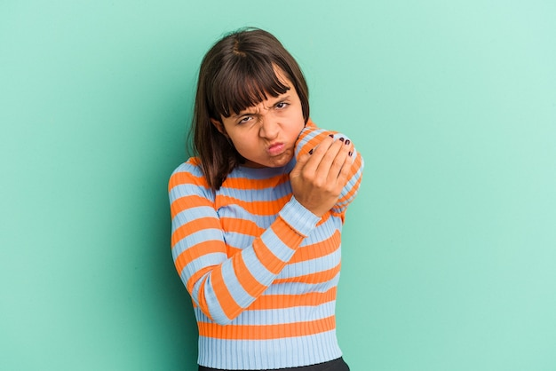 Giovane donna di razza mista isolata su sfondo blu che massaggia il gomito, soffrendo dopo un cattivo movimento.