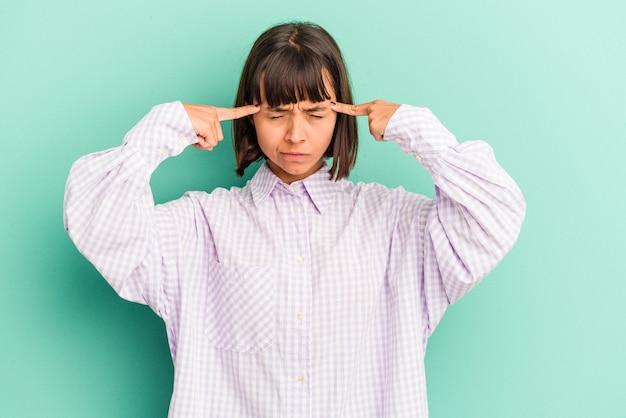Giovane donna di razza mista isolata su sfondo blu che punta al rialzo con la bocca aperta.