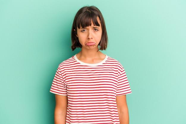 Giovane donna di razza mista isolata su sfondo blu che mostra un gesto di antipatia, pollice verso. concetto di disaccordo.
