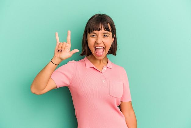 Giovane donna di razza mista isolata su sfondo blu che mostra un gesto di corna come un concetto di rivoluzione.