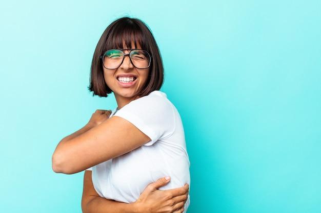 Giovane donna di razza mista isolata su sfondo blu che soffre di mal di schiena.