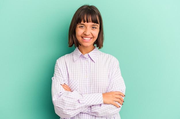 La giovane donna di razza mista isolata su sfondo blu soffre di dolore alla gola a causa di un virus o di un'infezione.