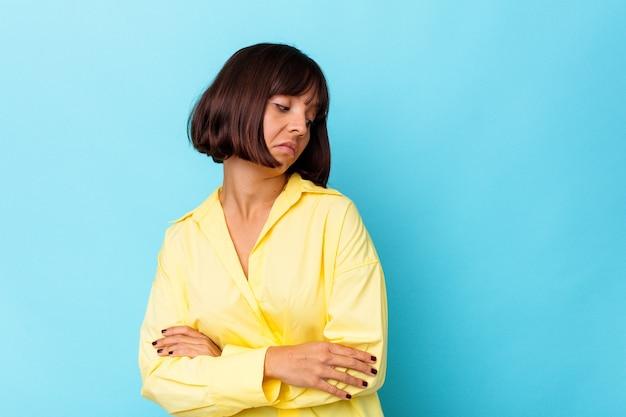 Giovane donna di razza mista isolata su sfondo blu stanca di un compito ripetitivo.