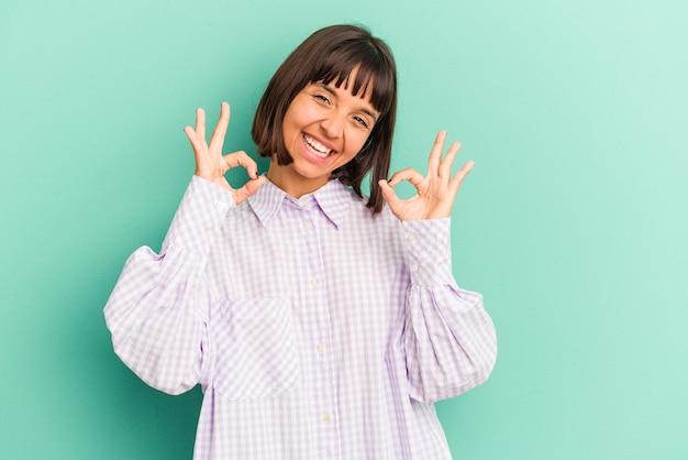 Giovane donna di razza mista isolata su sfondo blu che sbadiglia mostrando un gesto stanco che copre la bocca con la mano.