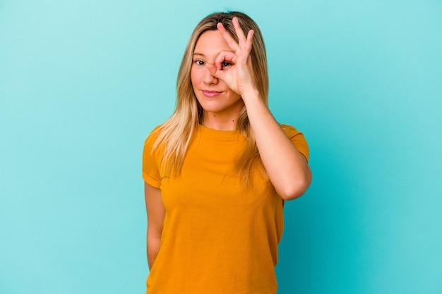 Giovane donna di razza mista isolata sul blu eccitato mantenendo il gesto giusto sull'occhio.