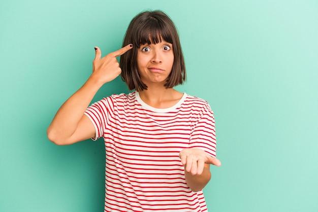 Giovane donna di razza mista isolata su blu che tiene e mostra un prodotto a portata di mano.