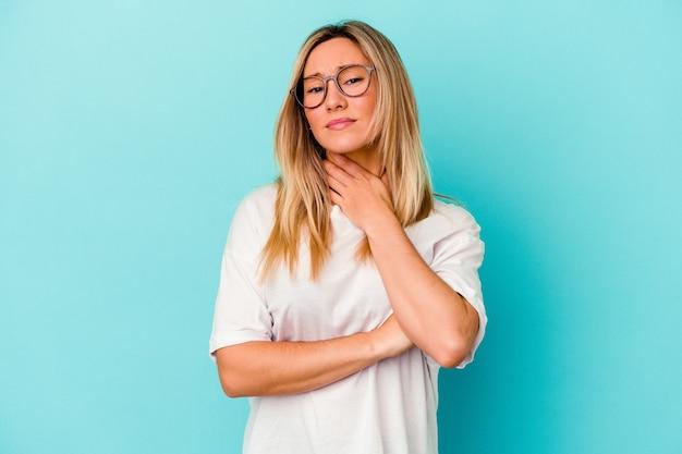 La giovane donna di razza mista isolata sul blu soffre di dolore alla gola a causa di un virus o di un'infezione.