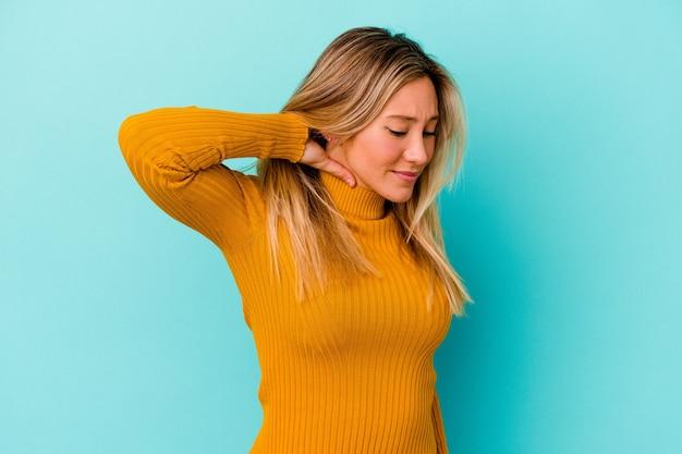 Giovane donna di razza mista isolata sulla parete blu che ha un dolore al collo a causa dello stress, massaggia e tocca con la mano.