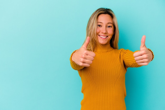 Giovane donna di razza mista isolata sul muro blu sorridendo e alzando il pollice