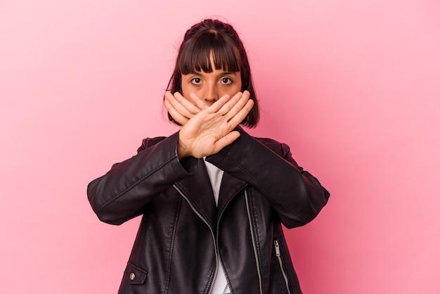 Giovane donna di razza mista isolata su sfondo rosa che fa un gesto di rifiuto