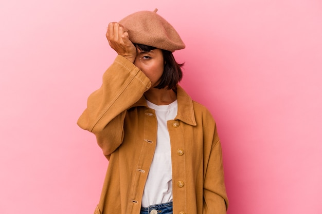 Giovane donna di razza mista isolata su sfondo rosa dimenticando qualcosa, schiaffeggiando la fronte con il palmo e chiudendo gli occhi.