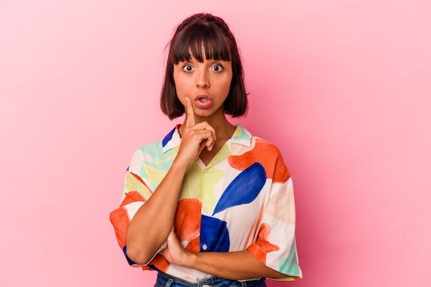 Giovane donna di razza mista isolata su sfondo rosa con qualche grande idea, concetto di creatività.