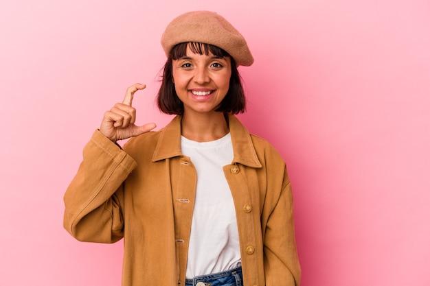 Giovane donna di razza mista isolata su sfondo rosa che tiene qualcosa di piccolo con l'indice, sorridente e fiducioso.