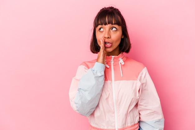 La giovane donna di razza mista isolata su sfondo rosa sta dicendo una notizia segreta di frenata calda e sta guardando da parte