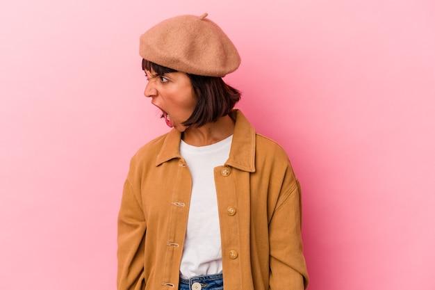 Giovane donna di razza mista isolata su sfondo rosa che grida molto arrabbiato, concetto di rabbia, frustrato.