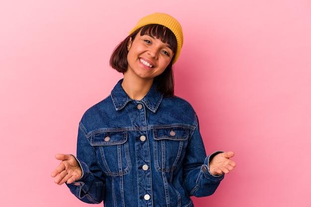 Giovane donna di razza mista isolata su sfondo rosa che mostra un'espressione di benvenuto.