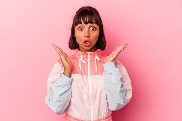 Giovane donna di razza mista isolata su sfondo rosa sorpresa e scioccata.