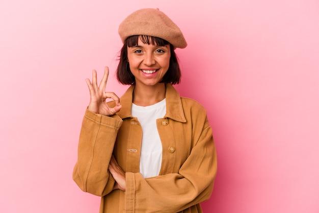 Giovane donna di razza mista isolata su sfondo rosa strizza l'occhio e tiene un gesto ok con la mano.