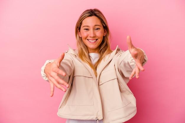 La giovane donna di razza mista isolata sul muro rosa si sente sicura di dare un abbraccio alla telecamera.