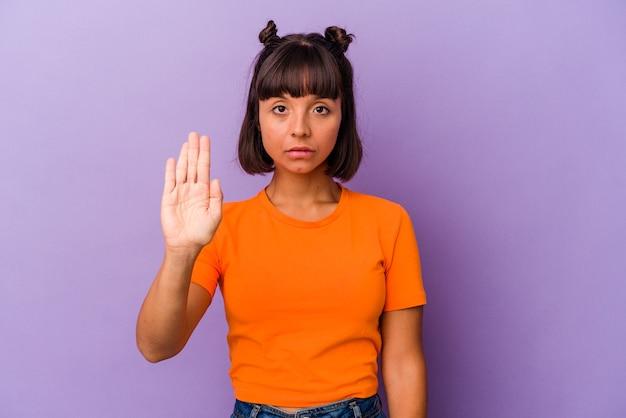 Giovane donna di razza mista isolata su sfondo viola in piedi con la mano tesa che mostra il segnale di stop, impedendoti.