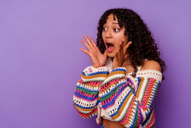 Giovane donna di razza mista isolata su grida viola ad alta voce, tiene gli occhi aperti e le mani tese.