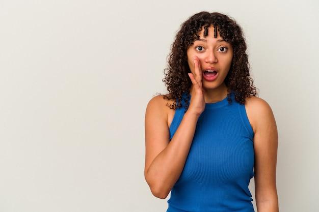 La giovane donna di razza mista isolata su sfondo bianco grida forte, tiene gli occhi aperti e le mani tese.