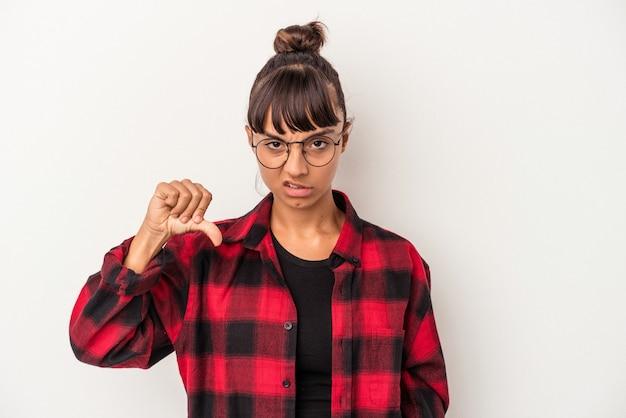 Giovane donna di razza mista isolata su sfondo bianco che mostra il pollice verso il basso, concetto di delusione.
