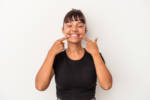 Giovane donna di razza mista isolata su sfondo bianco sorride, puntando il dito alla bocca.
