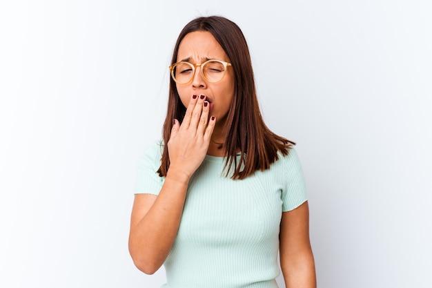 Giovane donna di razza mista isolata che sbadiglia mostrando un gesto stanco che copre la bocca con la mano.
