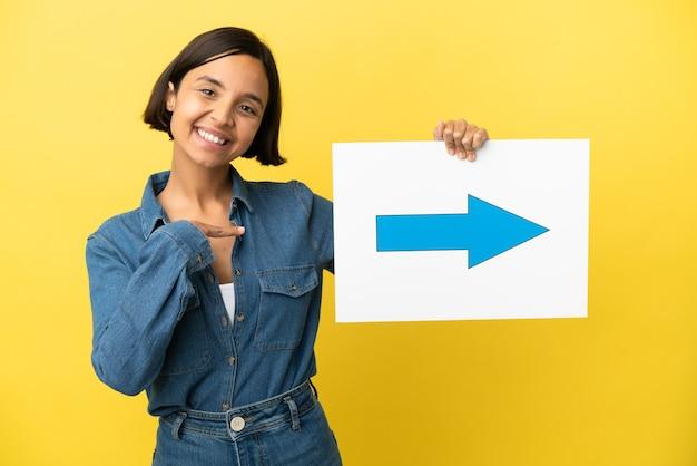 Giovane donna di razza mista isolata su sfondo giallo che tiene un cartello con il simbolo della freccia e lo indica