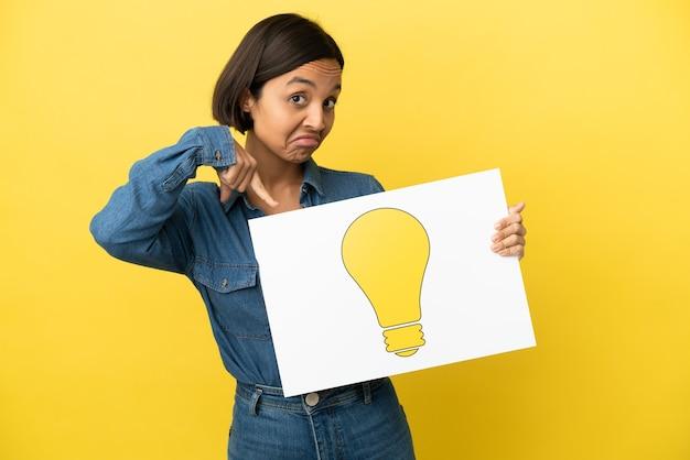 Giovane donna di razza mista isolata su sfondo giallo che tiene un cartello con l'icona della lampadina e lo punta
