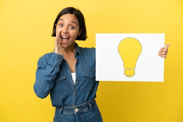 Giovane donna di razza mista isolata su sfondo giallo in possesso di un cartello con l'icona della lampadina e urlando