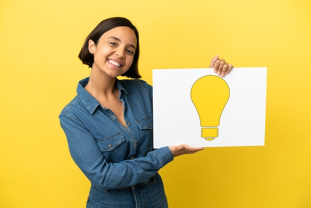 Giovane donna di razza mista isolata su sfondo giallo in possesso di un cartello con l'icona della lampadina con espressione felice