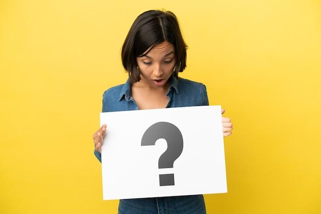 Giovane donna di razza mista isolata su sfondo giallo che tiene un cartello con il simbolo del punto interrogativo