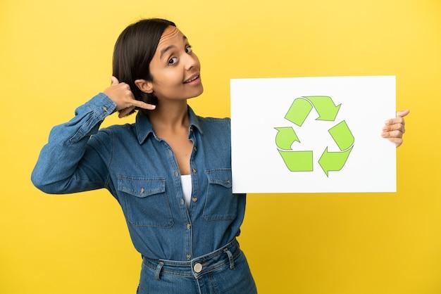 Giovane donna di razza mista isolata su sfondo giallo che tiene un cartello con l'icona di riciclo e fa il gesto del telefono phone