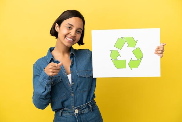 Giovane donna di razza mista isolata su sfondo giallo che tiene un cartello con l'icona di riciclo e punta verso la parte anteriore
