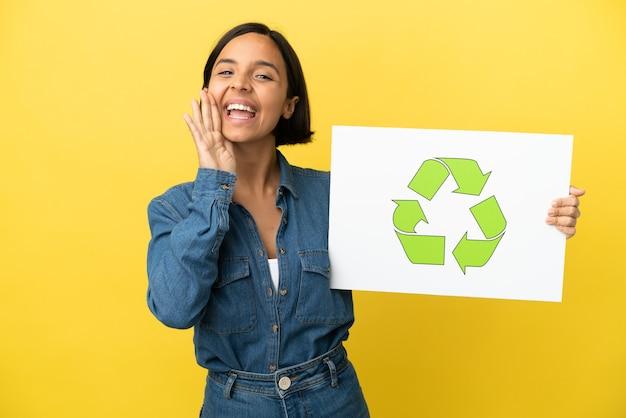 Giovane donna di razza mista isolata su sfondo giallo in possesso di un cartello con icona di riciclo e grida