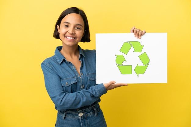 Giovane donna di razza mista isolata su sfondo giallo in possesso di un cartello con icona di riciclo con espressione felice