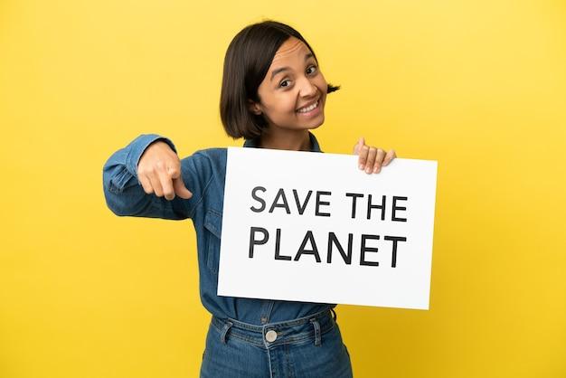 Giovane donna di razza mista isolata su sfondo giallo con in mano un cartello con il testo salva il pianeta e indicando la parte anteriore