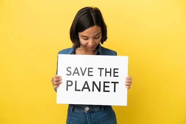 Giovane donna di razza mista isolata su sfondo giallo in possesso di un cartello con testo save the planet