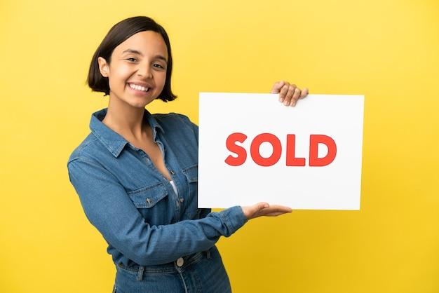 Giovane donna di razza mista isolata su sfondo giallo con in mano un cartello con testo venduto con espressione felice