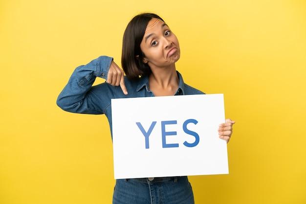 Giovane donna di razza mista isolata su sfondo giallo che tiene un cartello con il testo s e lo indica