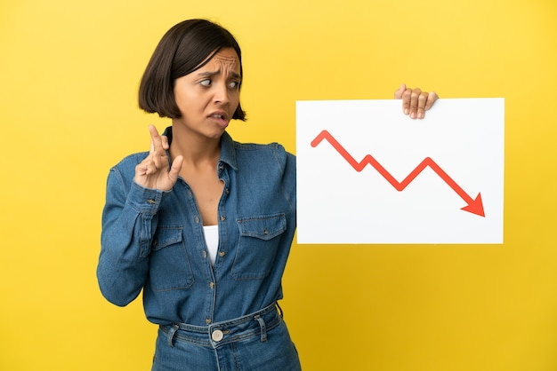 Giovane donna di razza mista isolata su sfondo giallo con in mano un cartello con un simbolo di freccia di statistiche decrescenti con le dita incrociate