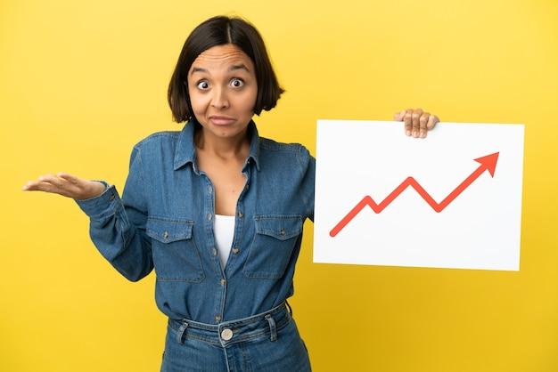 Giovane donna di razza mista isolata su sfondo giallo con un cartello con un simbolo di freccia statistica in crescita che ha dubbi